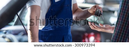 Car mechanic is giving keys to the fixed car  - stock photo