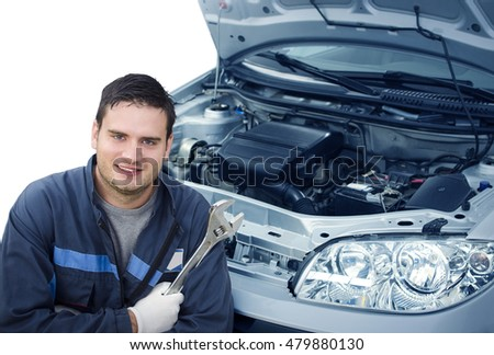 Car mechanic. Isolated mechanic holding wrench and standing next to the car with an opened hood. Car service.