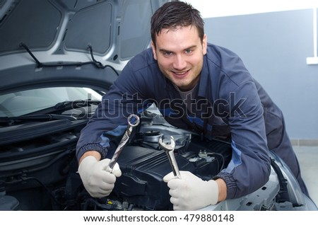 Car mechanic. Positive car mechanic holding wrenches ready to start working. Car service.