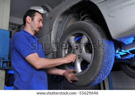 Car mechanic removing wheel nuts to change tire - a series of MECHANIC related images. - stock photo
