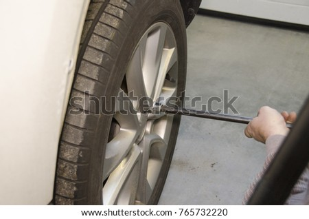 Car mechanic removing wheel nuts to check brakes in the car