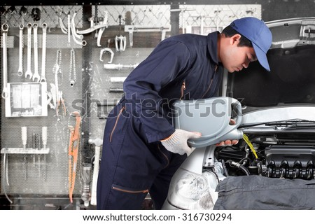 Car mechanic replacing and pouring oil into engine at maintenance repair service station with tools background - stock photo