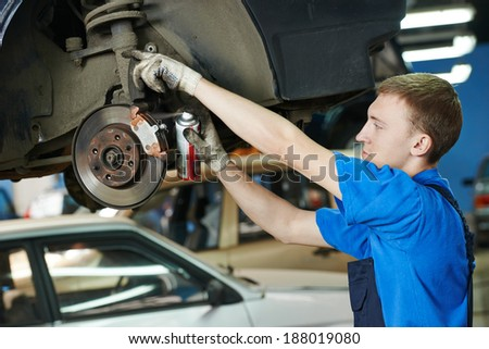 car mechanic replacing car wheel brake shoes of lifted automobile at repair service station - stock photo