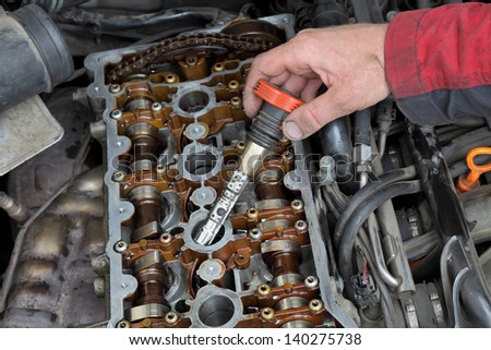 Car mechanic replacing ignition coil on gasoline engine