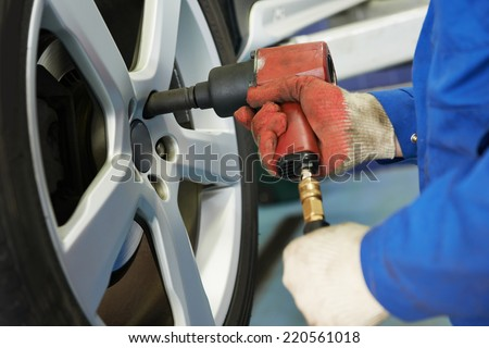 car mechanic screwing or unscrewing car wheel of lifted automobile at repair service station - stock photo