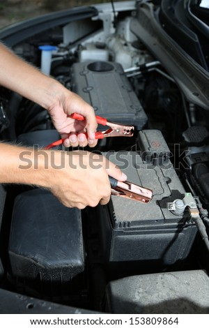 Car mechanic uses battery jumper cables to charge dead battery - stock photo