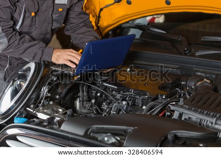 Car mechanic with a tablet making a diagnosis engine - stock photo