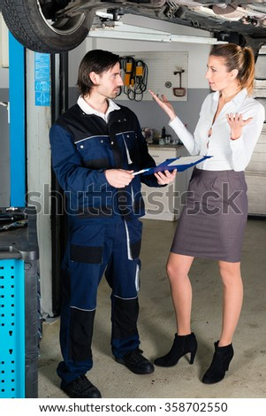 Car mechanic with angry female customer - stock photo