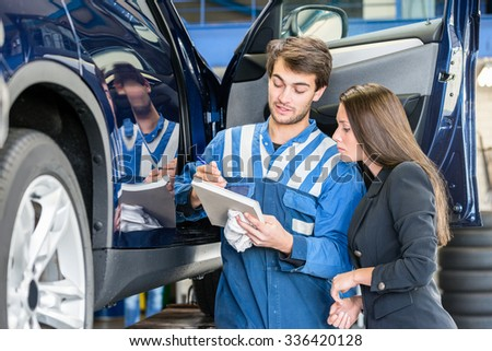 Car mechanic with female customer going through maintenance checklist in garage - stock photo