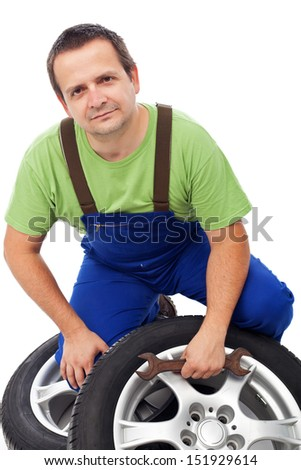 Car mechanic with new tires and double ended spanner - isolated - stock photo