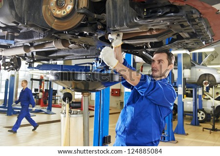car mechanic with spanner tighten car suspension detail of lifted automobile at repair service station - stock photo