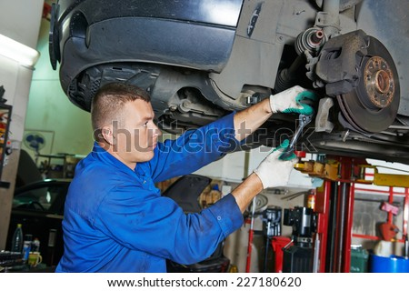 car mechanic worker repairing suspension of lifted automobile at auto repair garage shop station