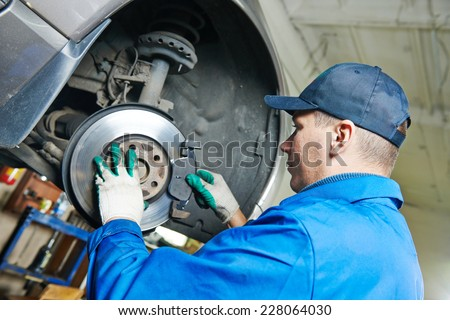 car mechanic worker replacing brakes of lifted automobile at auto repair garage shop station - stock photo