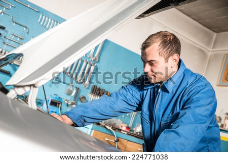 Car mechanic working in auto repair service - stock photo