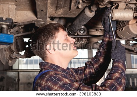 Car mechanic working in auto repair service station - stock photo