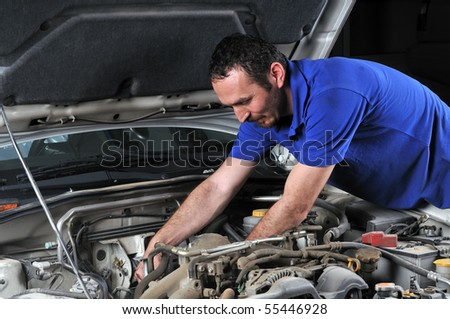 Car mechanic working on a car - a series of MECHANIC related images. - stock photo