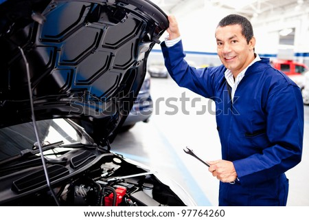 Car mechanic working on an engine at the repair shop - stock photo