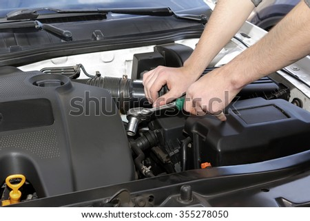 Car mechanic working under the engine hood of a car. - stock photo