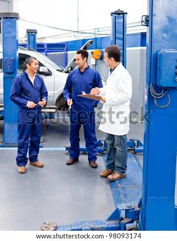 Car mechanics at the repair shop talking - stock photo
