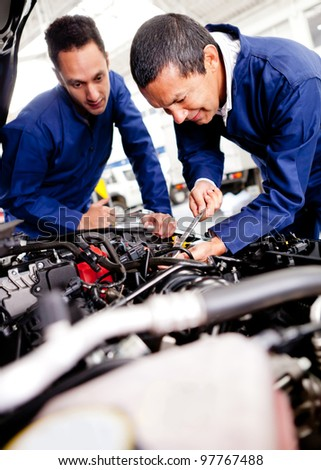 Car mechanics working on a broken engine - stock photo