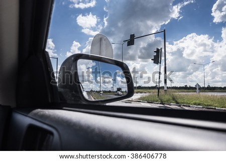 car mirror at cross roads - stock photo