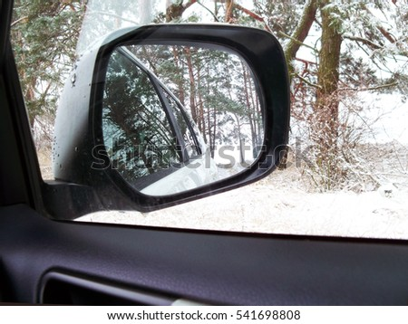 Car mirror. Forest in rear view mirror closeup. Reflected in a rearview. In the background forest. Winter