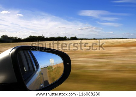 Car mirror with background speed blur - stock photo