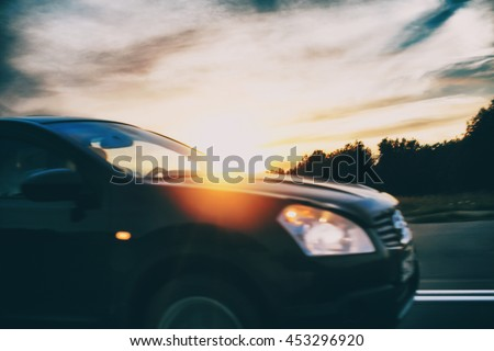 car moving rapidly on the road. car driving on the road in the rays of the setting sun. side view. blurred background and blurred motion due to the concept