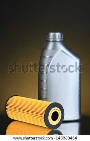 Car oil filter and motor oil can on dark color background - stock photo