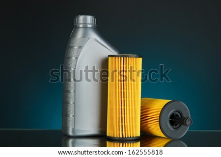 Car oil filters and motor oil can on dark color background - stock photo