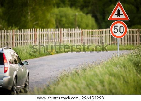 Car on a country road with limited speed and crossroad sign - stock photo