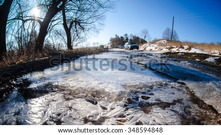 Car on a dangerous stretch of road covered with snow and ice. Sunny frosty morning. - stock photo
