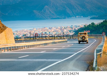 car on a mountain road and city - stock photo