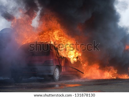 Car on fire after and accident or during a riot. - stock photo