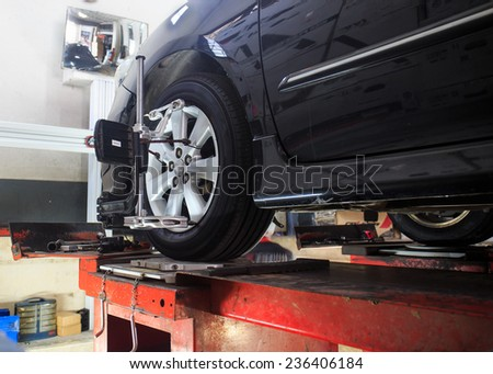 Car on stand with sensors on wheels for wheels alignment camber check in workshop of Service station. - stock photo