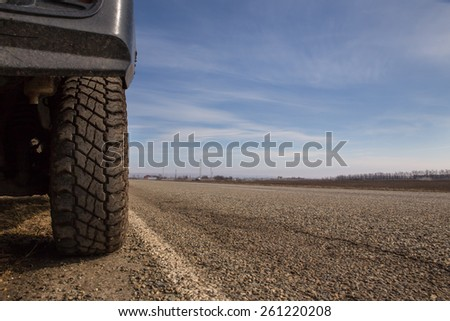 Car on the highway. Wheel on the pavement, close-up. - stock photo