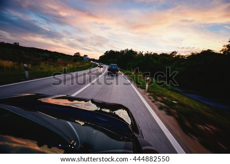 Car on the road in sunset. - stock photo
