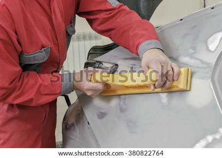 Car painter prepares the rear wing of the car for painting. - stock photo