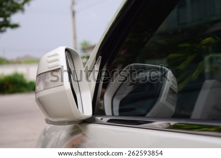 car parking with side rear-view mirror closed for safety - stock photo