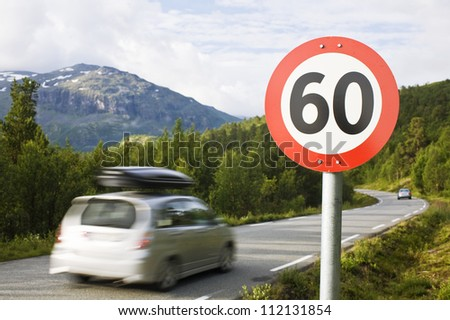 Car passing speed limit sign - stock photo
