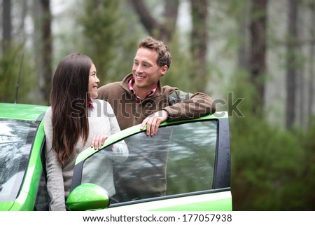 Car people - happy couple driving on road trip in green new rental car in beautiful nature forest. Romantic multiracial couple on the road on vacation. Asian woman, Caucasian man.
