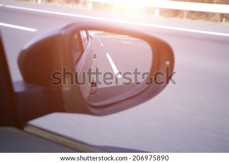 car rear mirror view on high way - stock photo