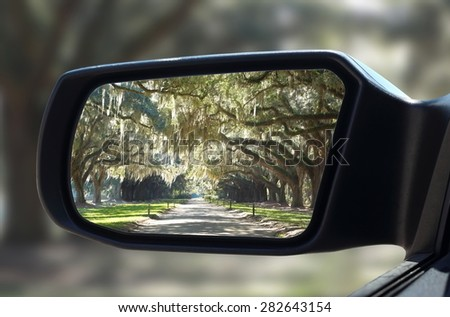 Car Rear-view mirror in reflection forest live green oak trees that hang down in unique pattern. Dirt road leading up to a slavery plantation  - stock photo