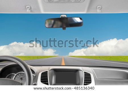 Car rear view mirror inside the car and drive a car on road with blue sky background.