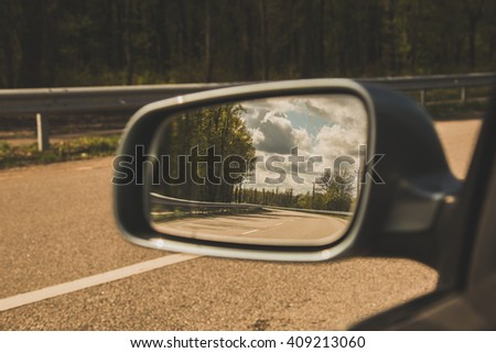 Car Rearview Mirror reflected the road - stock photo