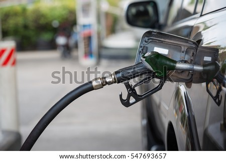 Car refueling on a petrol station ; filling petrol or gas tank at gas station.