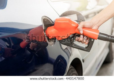 Car refueling on petrol station. To fill the machine with fuel. Car refueling with gasoline at gas station. Fuel pump at station. Man pumping gasoline fuel in car at gas station.