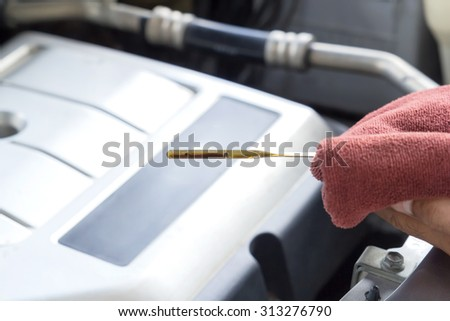 Car repair service, Auto mechanic checking oil level in a engine - stock photo