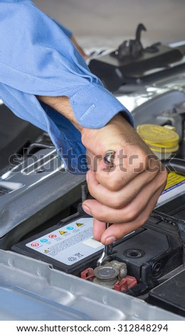 Car repair service, Auto mechanic checking the clamp nut of a car battery with a wrench - stock photo