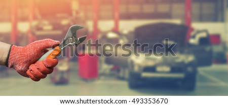 Car repairing,Hand of technician auto mechanic with a wrench working in garage. service in auto repair station.vintage tone,for banner